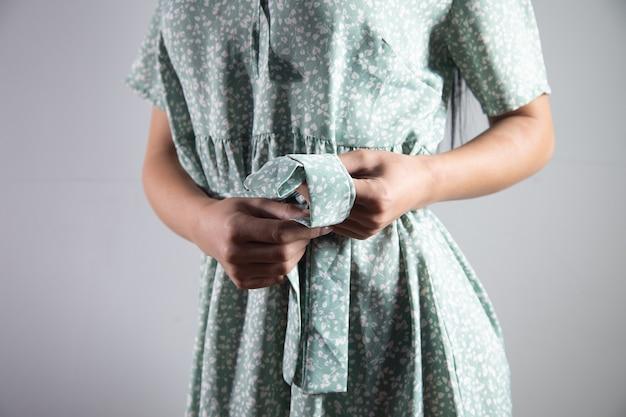 Vrouw knoopt een knoop in de taille van haar jurk
