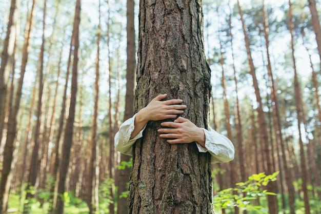 Vrouw knuffelde een boom met liefde in het bos