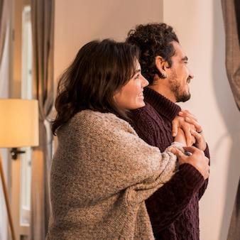 Vrouw knuffelen haar man van achteren