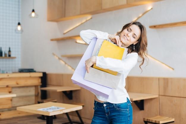 Vrouw knuffelen papieren zakken in café