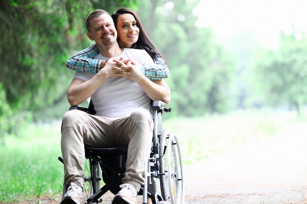 Vrouw knuffels man in rolstoel