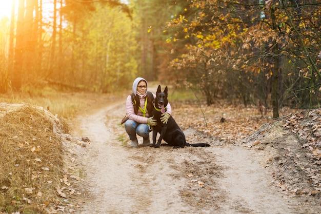 Vrouw knuffelt een hond tijdens het wandelen in het bos