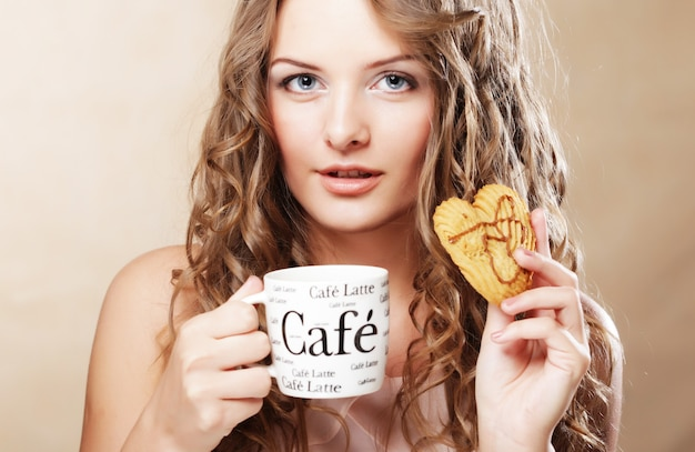 Vrouw koekje eten en koffie drinken. leuk schattig mooi jong vrouwelijk model.