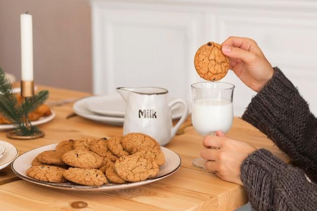 Vrouw koekje in melk onderdompelen