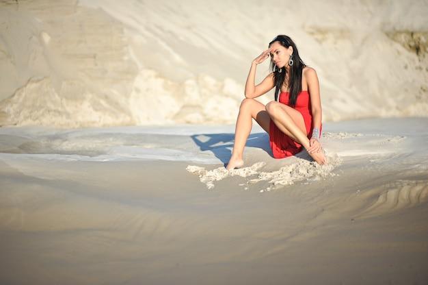 Vrouw koelen op het zand in rode jurk