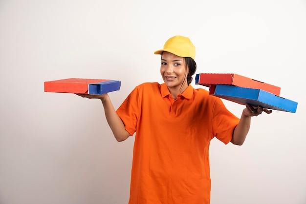 Vrouw koerier in uniform bedrijf stelletje pizza's.