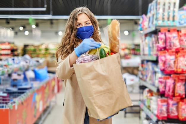 Vrouw koerier vrijwilliger in een medisch masker houdt een papieren zak met producten en groenten.