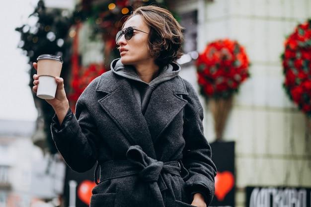 Vrouw koffie drinken buiten de straat