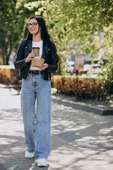 Vrouw koffie drinken en houden afhaalmaaltijden dozen met voedsel