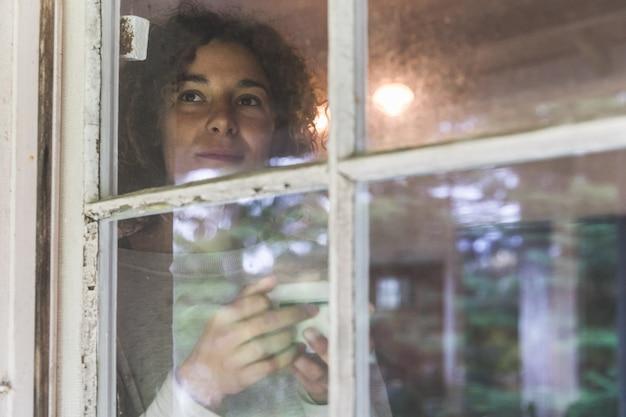 Vrouw koffie drinken en kijkt uit door een oud raam