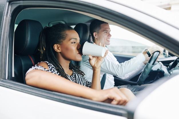 Vrouw koffie drinken in de auto