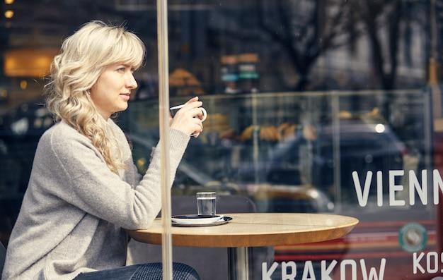 Vrouw koffie drinken in de ochtend bij restaurant soft focus op de ogen