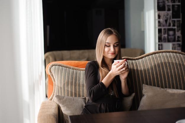 Vrouw koffie drinken in de ochtend in een restaurant