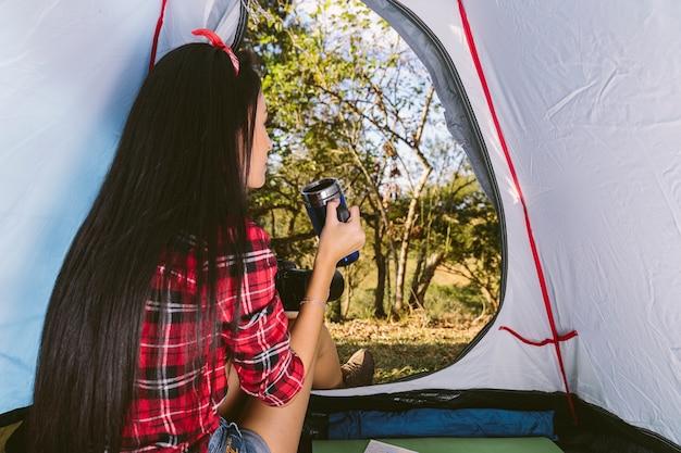 Vrouw koffie drinken in de tent