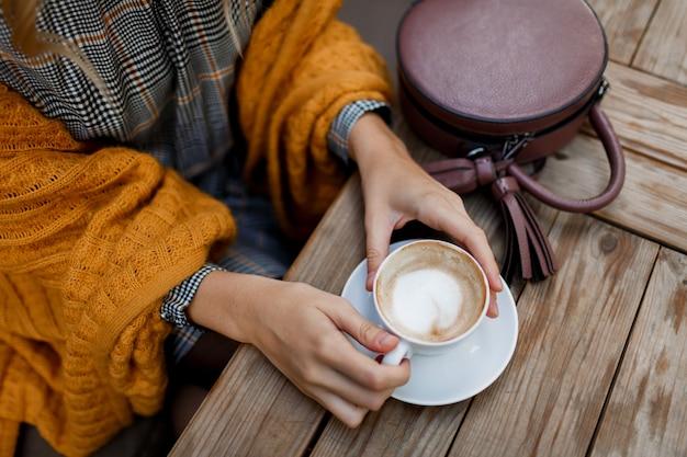 Vrouw koffie drinken. stijlvolle tas op tafel. grijze jurk en oranje plaid dragen. genieten van een gezellige ochtend in café.