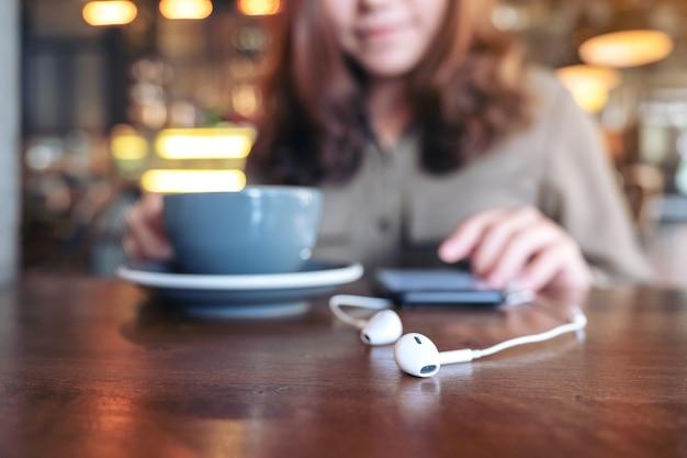 Vrouw koffie drinken tijdens het gebruik van mobiele telefoon om muziek te luisteren met oortelefoon op houten tafel in café