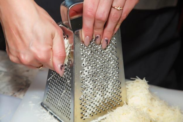 Vrouw-kok wrijft kaas op rasp voor de bereiding van zelfgemaakte italiaanse pizza op plastic snijplank. rasp kaas op grote rasp in keuken. concept van culinaire uitmuntendheid en catering. ruimte kopiëren