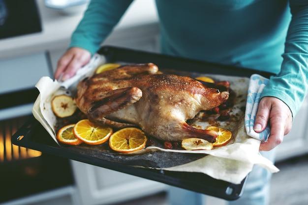 Vrouw koken eend met groenten en zet het uit de oven.