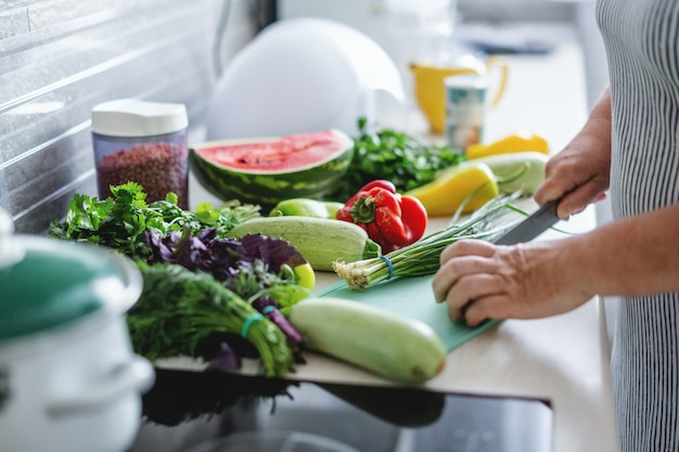 Vrouw koken groenten in de keuken.