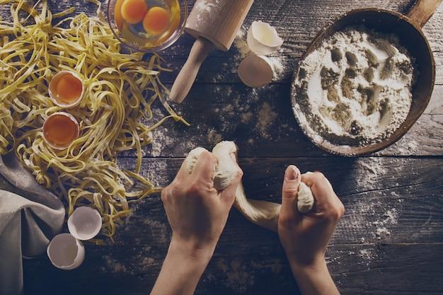 Vrouw koken handen voorbereiding maken van lekkere zelfgemaakte klassieke italiaanse pasta op houten tafel. detailopname. top view. toning.