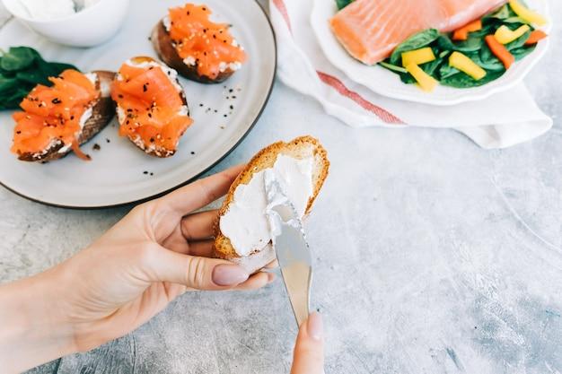 Vrouw koken heerlijke toast met zalm en kaasroom, close-up.