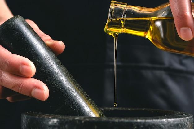 Vrouw koken met olijfolie en mortel in de keuken