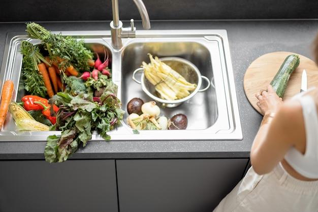 Vrouw koken met verse groenten en groenten in de gootsteen