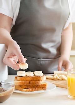 Vrouw koken zoete toast met pindakaas en banaan. europees ontbijt met toast en sap.
