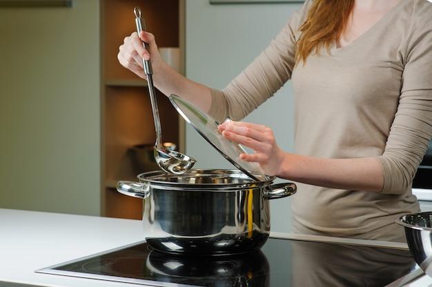 Vrouw kookt de soep in de keuken