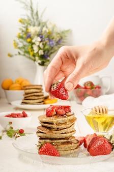 Vrouw kookt ontbijt en versiert een stapel pannenkoeken met aardbeien