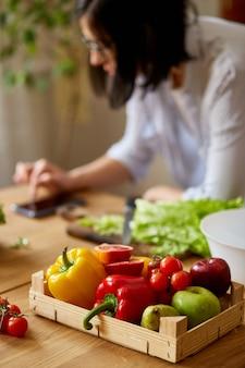 Vrouw kookt thuis in de keuken, met behulp van digitale tablet