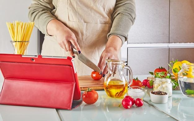 Vrouw kookt volgens de tutorial van online virtuele masterclass, en kijkt naar het digitale recept, gebruikt een touchscreen-tablet terwijl ze thuis een gezonde maaltijd kookt in de keuken.
