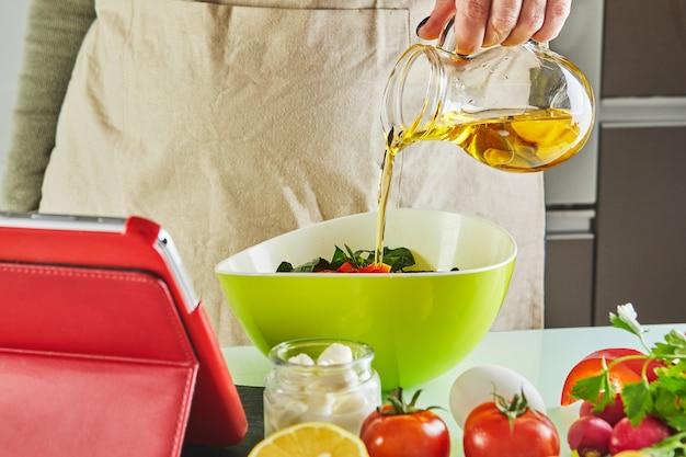 Vrouw kookt volgens de tutorial van online virtuele masterclass, en kijkt naar het digitale recept, met behulp van touchscreen-tablet
