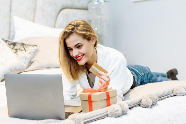 Vrouw koopt cadeautjes, bereidt zich voor op kerstmis, dichtbij geschenkdoos.