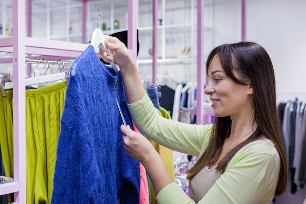 Vrouw koopt een blauwe trui in een winkelcentrum.