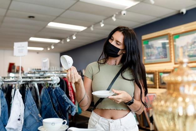 Vrouw koopt huishoudelijke artikelen in een tweedehandswinkel