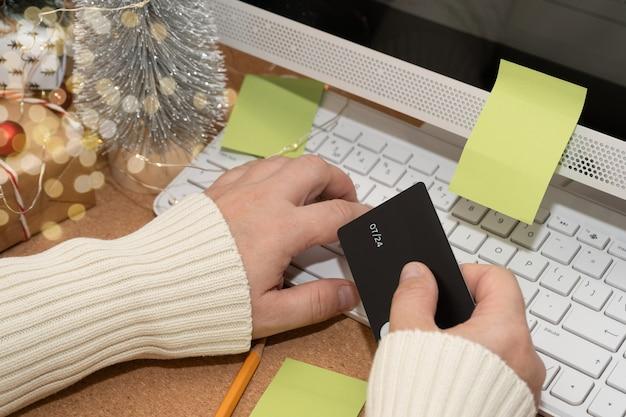 Vrouw koopt kerstcadeaus online betalen met creditcard met behulp van computer wintervakanties verkopen