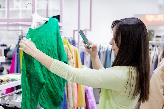 Vrouw koopt kleding in de uitverkoop shopping