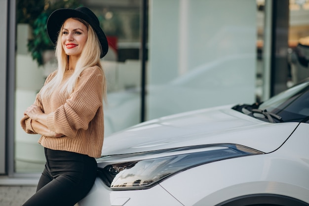 Vrouw koopt nieuwe auto in autoshowroom