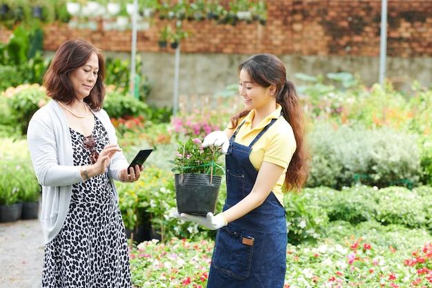 Vrouw koopt plant in tuincentrum