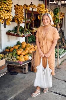 Vrouw koopt vers fruit op exotische lokale markt