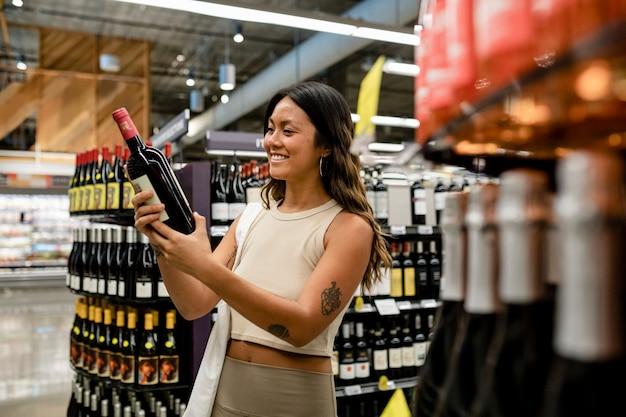 Vrouw koopt wijn, supermarkt winkelen hd-afbeelding
