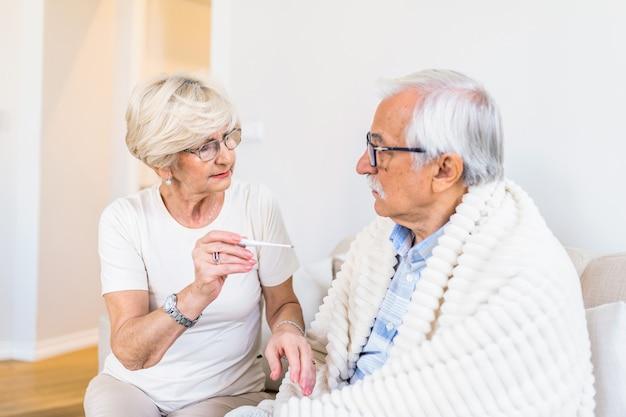 Vrouw koorts temperatuur van senior man zittend op bed controleren