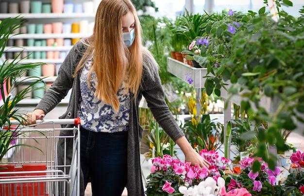 Vrouw kopen bloemen boodschappenwagentje tuincentrum