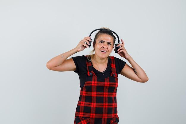 Vrouw koptelefoon in schort jurk opstijgen en op zoek onderbroken. vooraanzicht.