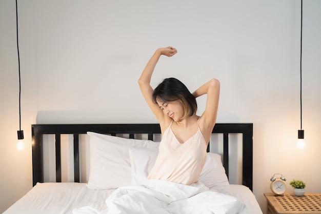 Vrouw kort haar die zich uitstrekt in bed na het wakker worden, achteraanzicht