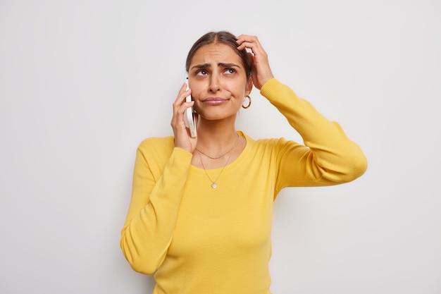 Vrouw krabt aan haar hoofd denkt dat iets zich ongelukkig voelt telefoneert houdt mobieltje in de buurt van oor gekleed in casual gele trui op wit