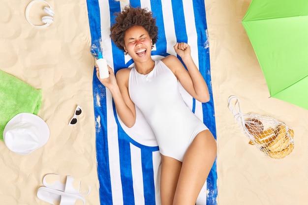 Vrouw kreeg zonnebrand op gezicht roept luid houdt fles zonnebrandcrème draagt witte zwembroek poses op handdoek op het strand zonnebaadt tijdens de zomerdag brengt vakanties in de buurt van zee door. veilig bruin worden
