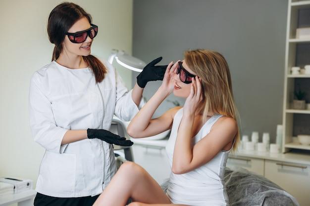 Vrouw krijgt consult voor laserbehandeling op haar hand in een schoonheidssalon.