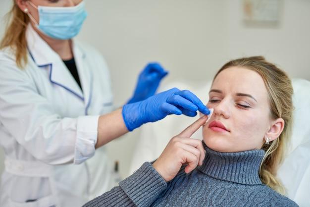 Vrouw krijgt cosmetische injectie van botox in de buurt van ogen, close-up